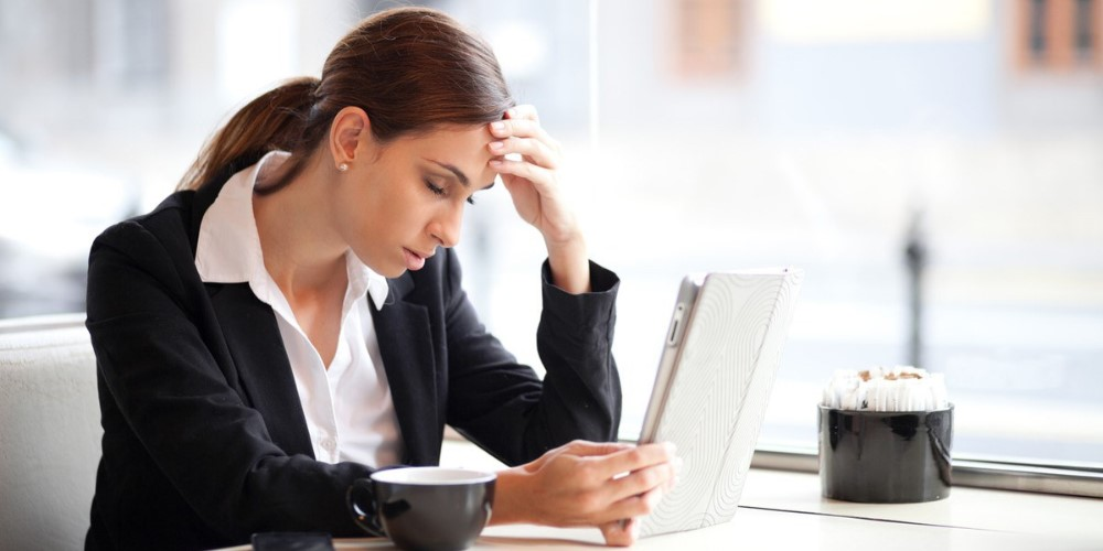 Woman looking upset whilst on computer