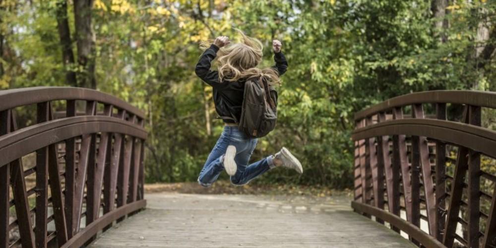 Woman jumping on bridge in joy