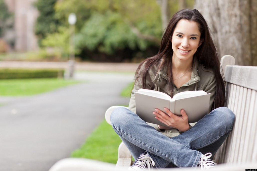 Girl sitting on bench with a book in her lap whilst smiling