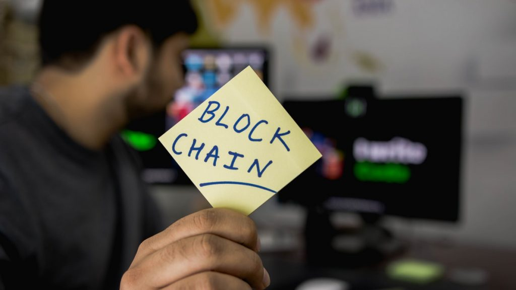 A guy holding a Blockchian card