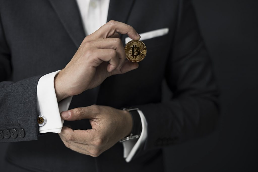Picture of man holding bitcoin