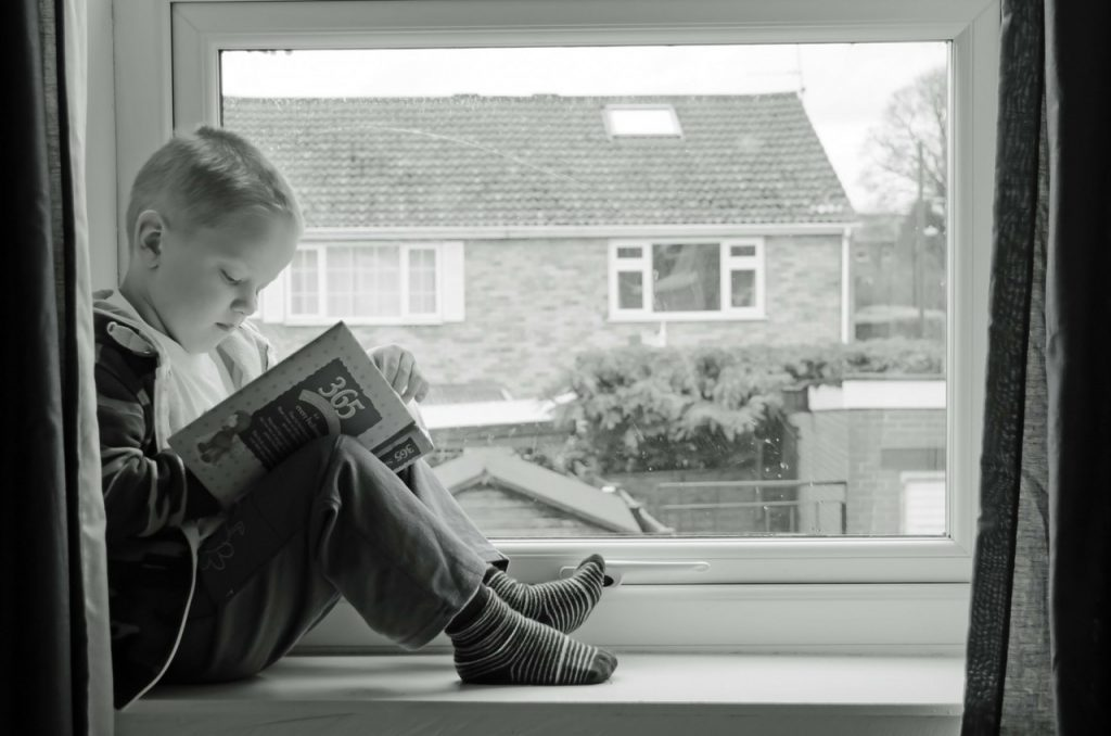A kid reading story book sitting on a window sill