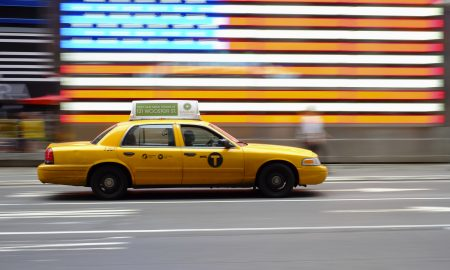 Yellow Taxi in NYC and a US flag in the background