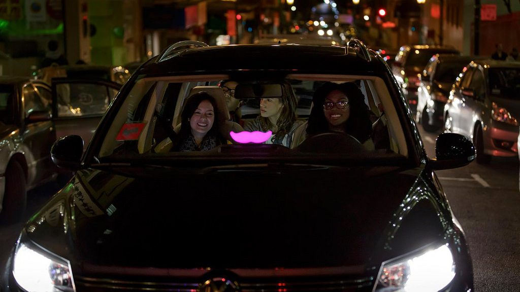 Passengers inside a car with Lyft's brand sign