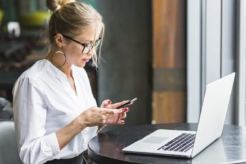 mulher de oculos mexendo no celular com computador na frente