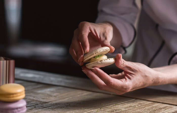 Photo of two hands making a macaron pastry