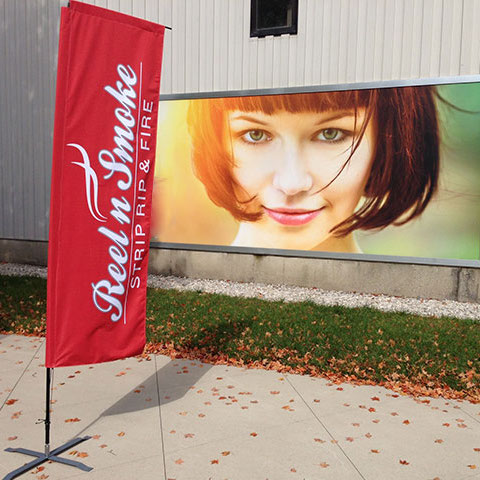 A red printed marketing flag on cross base used for event marketing.