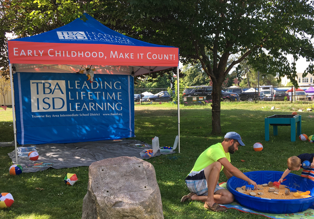 Children playing in sandbox in-front of pop-up tent printed with Early Childhood branding.