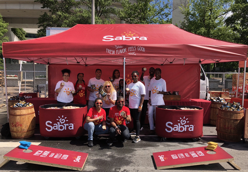 10x20 pop-up tent with Sabra branding that includes matching walls, corn hole games and sampling team.