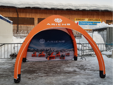 Ariens branded 10x10 GYBE inflatable tent outside in snow with custom printed back wall