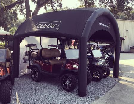A black Nitrox AIRFRAME inflatable tent used to protect two Club Car vehicles.