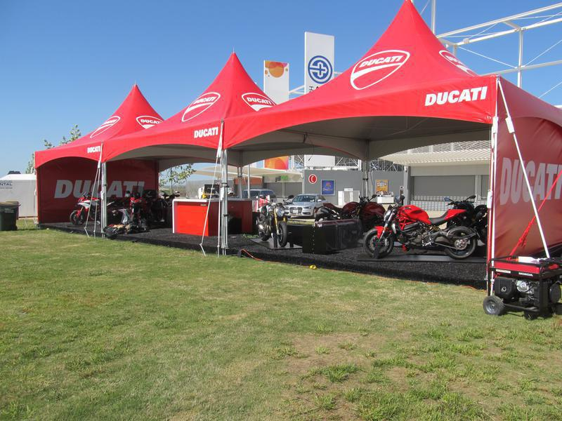 three 20x20 red Ducati frame tents with multiple motorcycles displayed underneath