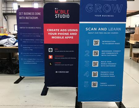 three small media backdrop walls that display directions about mobile apps for businesses