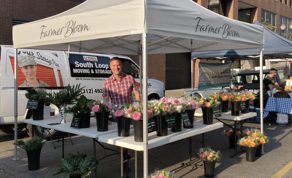 branded 10x10 pop-up tent at farmers market selling flowers