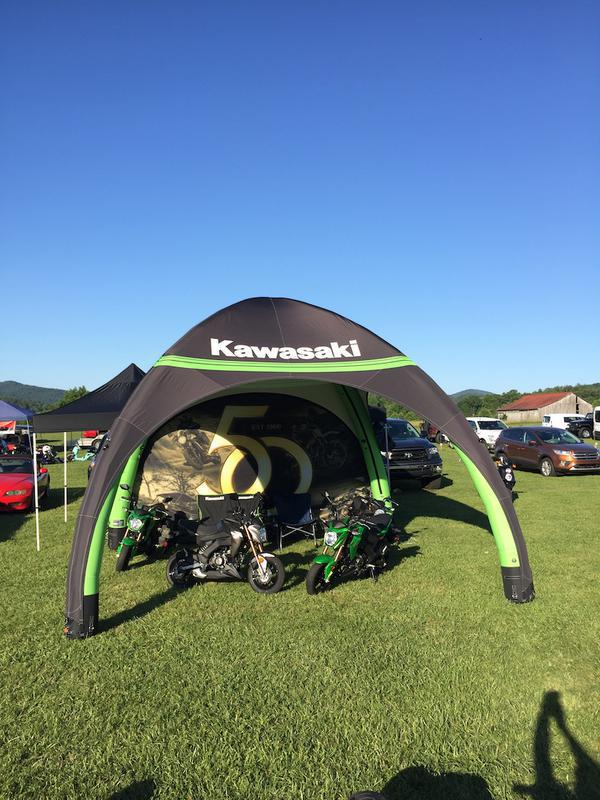 17x17 Kawasaki branded inflatable GYBE tent with two motorcycles displayed underneath at vehicle event