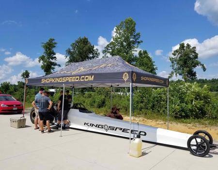 top fuel dragster and race team underneath custom printed 10x20 pop-up tent