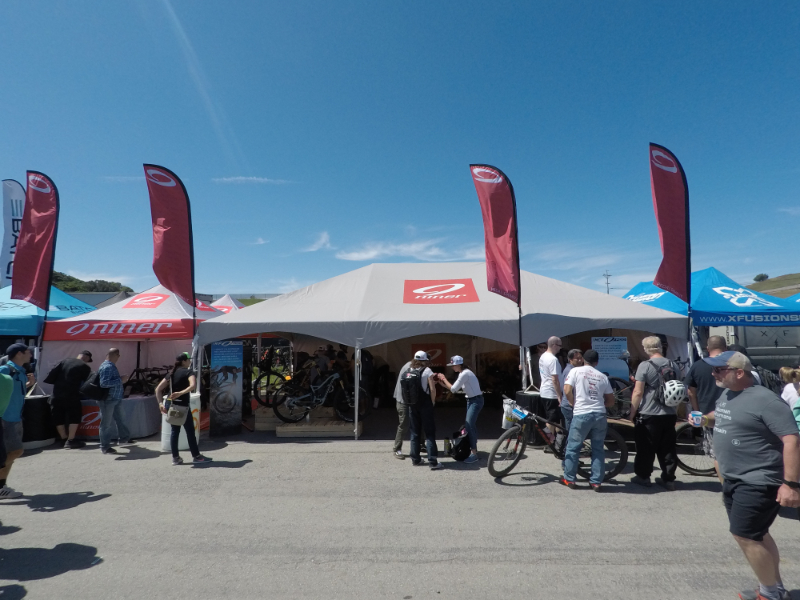 20x30 frame tent with custom printed canopy and feather flags for Niner Sea Otter Classic bicycle festival