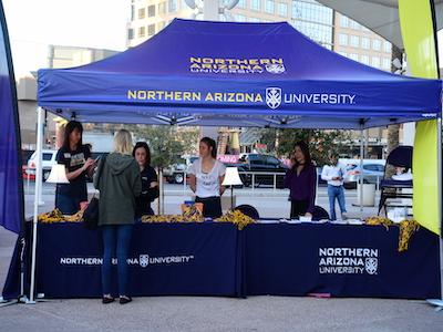A blue pop-up tent with Northern Arizona University logos.