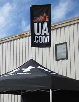 A peak flag on top of a heavy-duty pop-up tent.