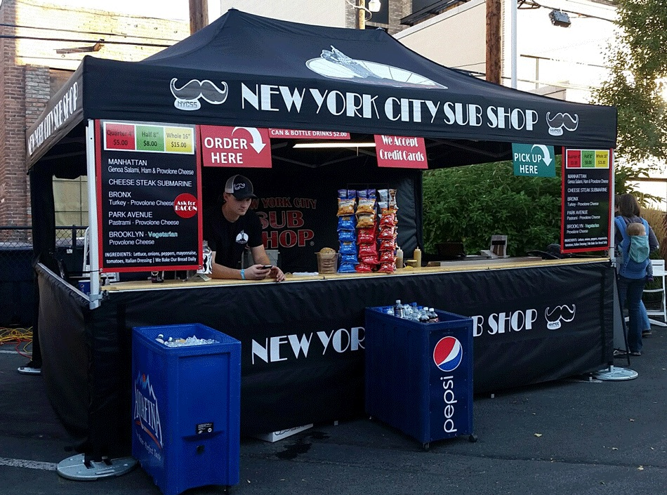 A 10x15 heavy-duty pop-up tent with full, half walls and countertops used for food concessions for a New York City Sub Shop