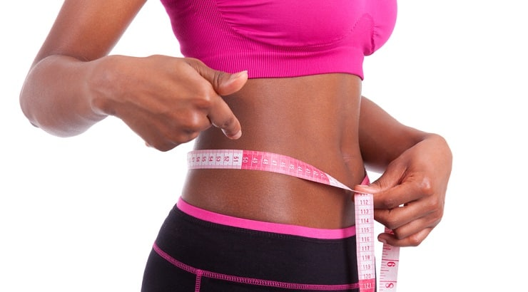 Black woman measuring her waist and being encouraged