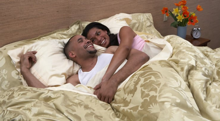 African Amrerican couple smiling in bed