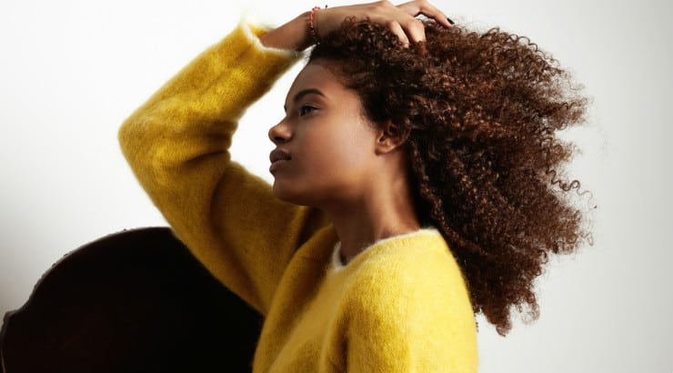 A black woman touching her hair