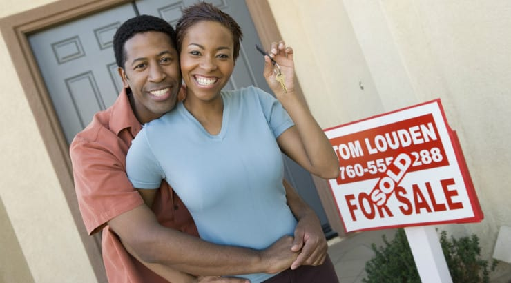 A young African American couple holding the keys to their new home