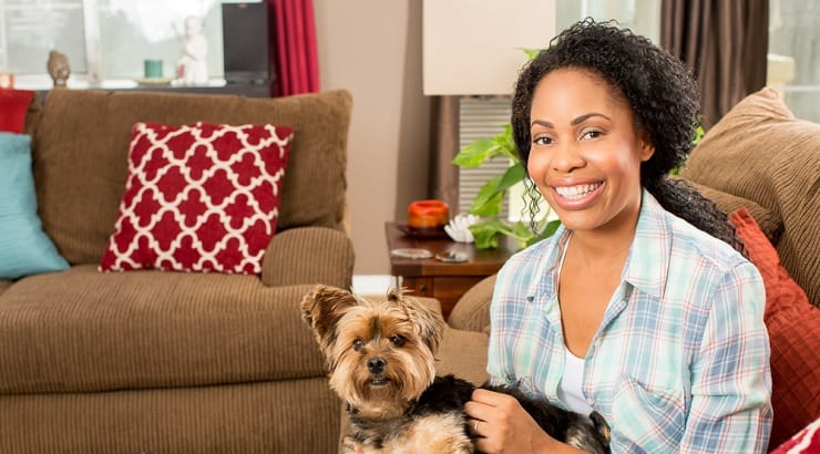 African American woman sitting in her new done up living room with her pet dog