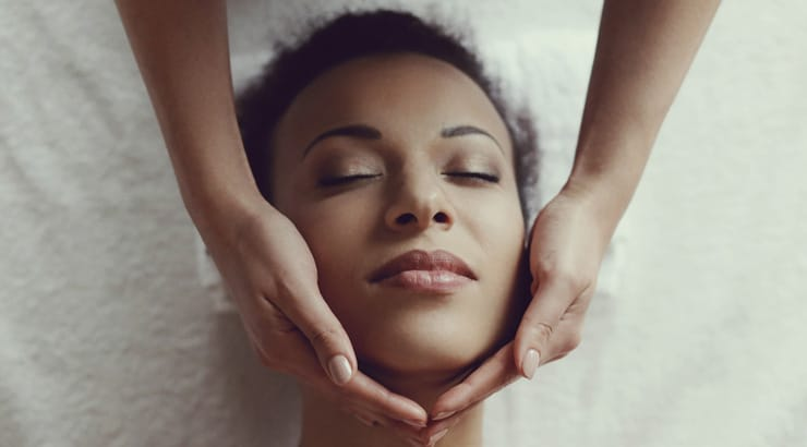 Black woman getting a facial with essential oils