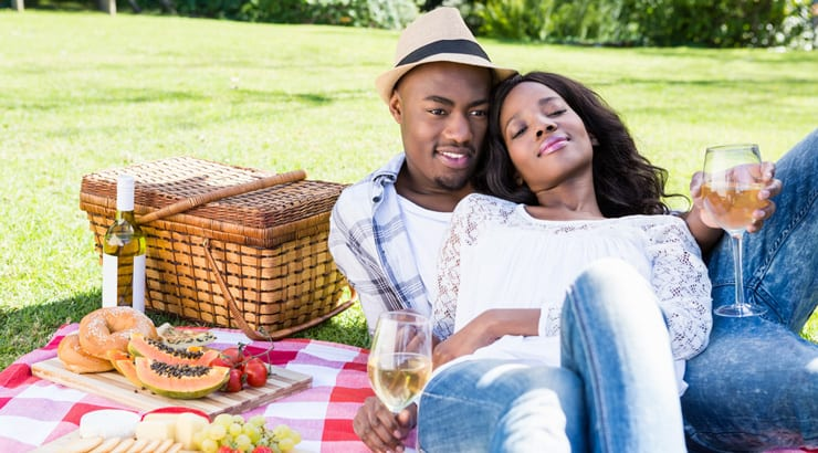 Young black couple having picnic date outside