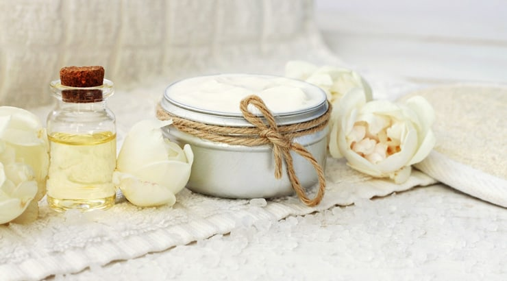Body butter surrounded by cream peonies on a spa towel