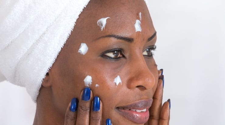 Beautiful Black Woman Applying a Light Face Cream