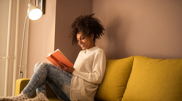 Black Woman Reading The Curly Girl Method Book Which She Bought