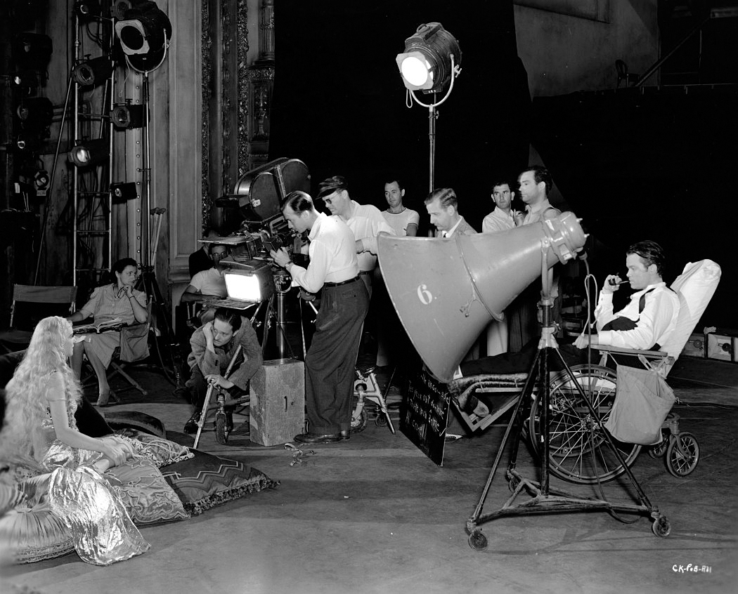 Shooting the classic Citizen Kane (1940), Gregg Toland, ASC can be seen crouching directly below the camera, while Orson Wells directs from a wheelchair at right, recovering from a leg injury.