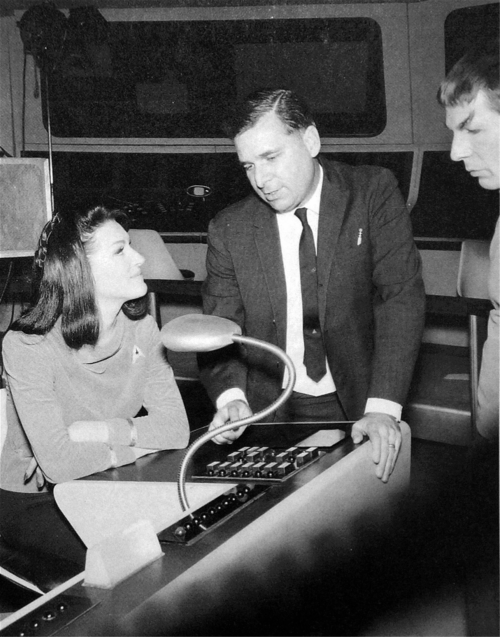 "On the bridge set, Trek creator Gene Roddenberry is flanked by Majel Barrett and Leonard Nimoy while filming the first series pilot ""The Cage."""