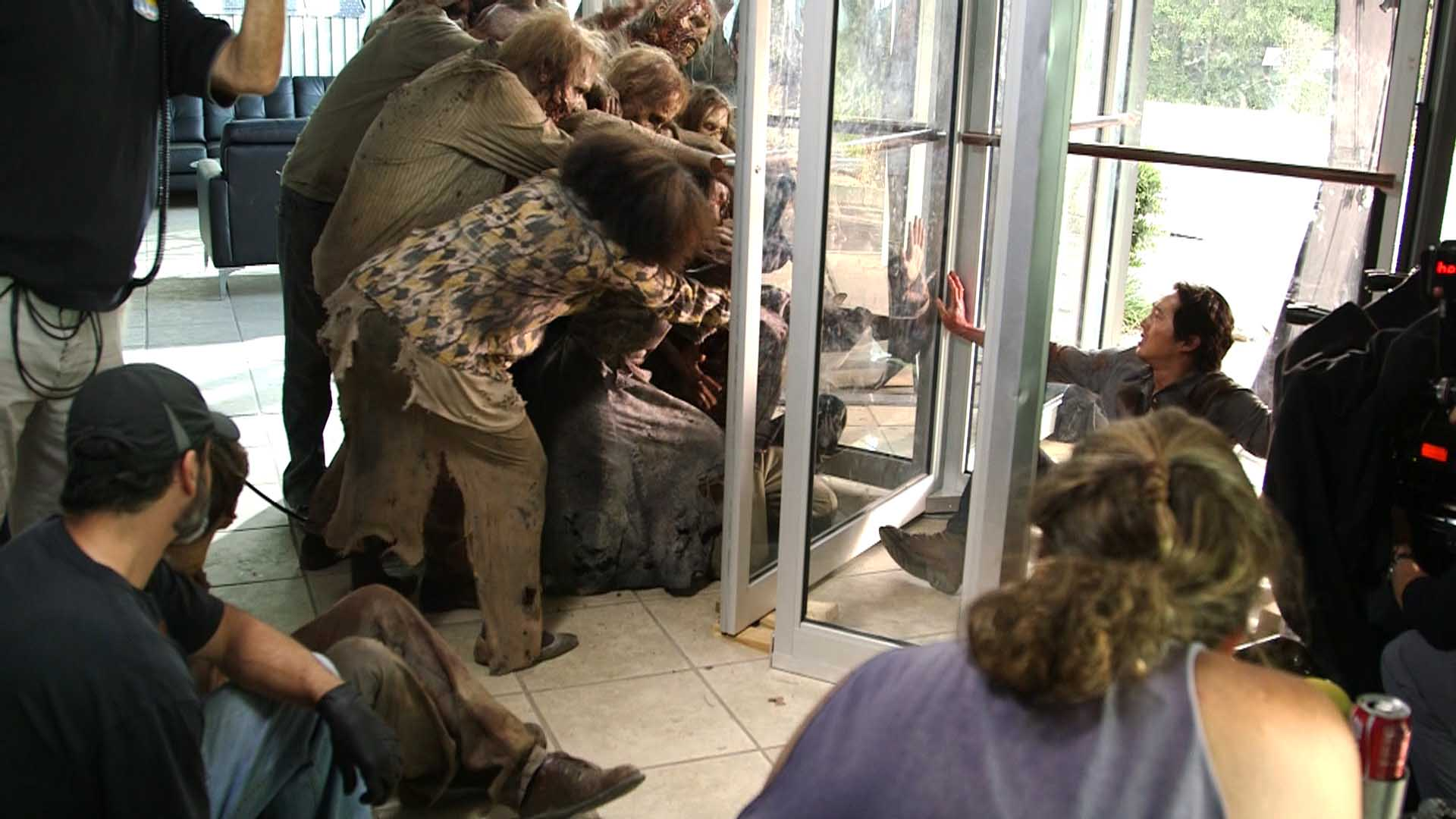 "Filming the Walking Dead episode ""Spend,"" as actors Tyler James Williams and Stephen Yeun are trapped by ""walker"" extras in a revolving door."