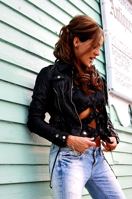 Pancara is wearing torn jeans and a leather jacket from the 80s with a hairstyle from the 50s.
