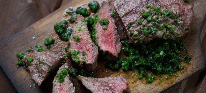 Sliced beef barbecue steak with chimichurri sauce, studio shot