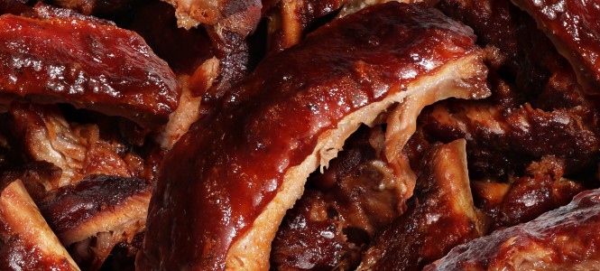 Ribs grilled barbecue meat with a close up view of a group of delicious cooked marinated spare rib as  gourmet food for dinner at a restaurant or backyard BBQ grill.