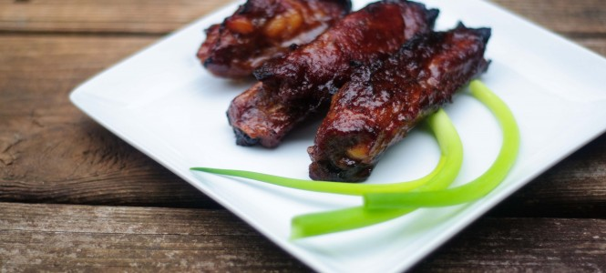 Chinese pork ribs with scallions on a white square plate