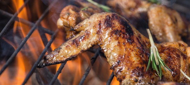 Delicious chicken wings on garden grill, close-up