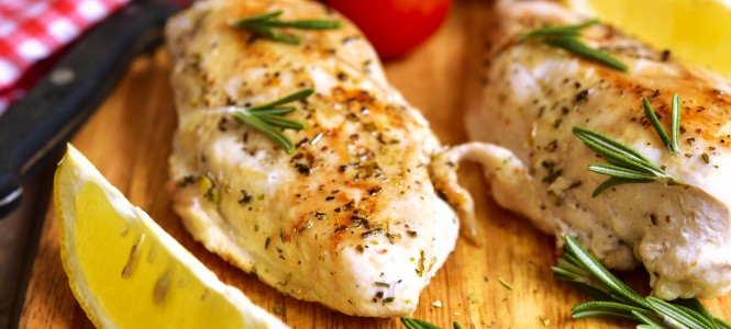 Chicken breast baked with rosemary on a cuuting board.