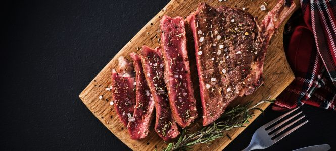 Entrecote. Steak on the bone. Rib eye. Tomahawk steak on the on a cutting board with rosemary. Roasting - Rare.