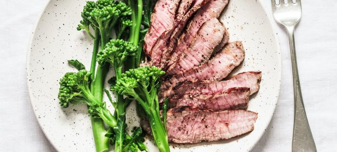 Fitness diet healthy lunch - grilled beef steak and boiled broccoli on a light background, top view