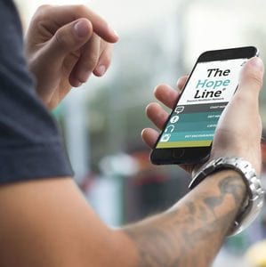 Guy with tattoo downloading TheHopeLine mobile app to get help for relationship problems