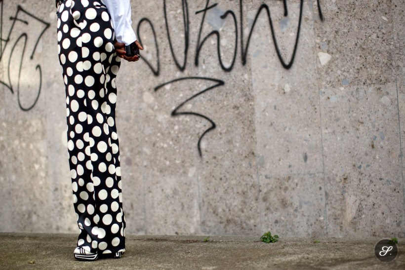 women wearing pants with a lot of dots on a street style photo taken in Milan during women's fashion week