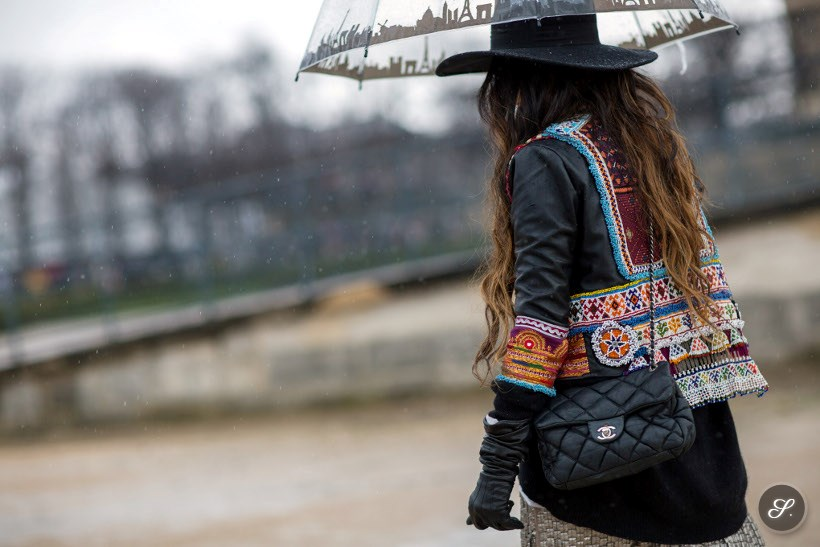 Angela Rozas Saiz before Elie Saab during Paris Women's Fashion Week Fall/Winter 2014. Angela is wearing a hat, leather jacket, gloves and beats the rain with an umbrella.