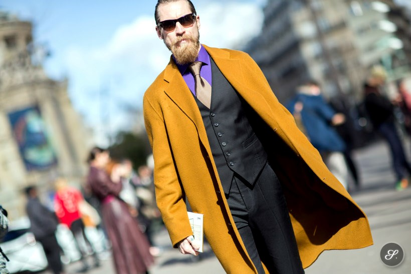 Justin O'Shea before Miu Miu during Paris Ready to Wear Women's Fashion Week Fall/Winter 2014. He is wearing a yellow coat for men.