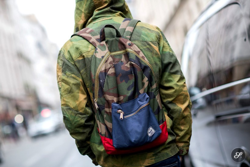 Men wearing a camouflage military jacket and backpack on a street style photo taken in Paris.